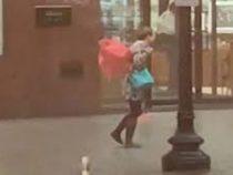Сильный ветер сломал женщине зонтик